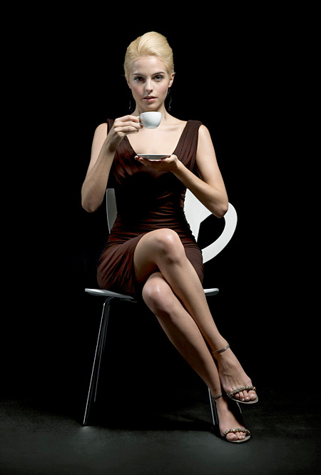 Lady in coffee dress on coffee chair.